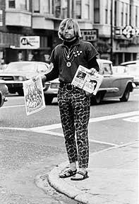 Newspaper hawker selling issues of The Berkeley Barb and The San Francisco Oracle on the corner of Haight and Ashbury, 1967 / © Larry Keenan.